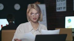 Mujer de negocios feliz que mira informe financiero en oficina oscura almacen de video