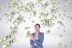 Mujer de negocios feliz que mira la lluvia del dinero contra el fondo blanco Imagen de archivo