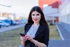 Mujer de negocios feliz que mira smartphone Fotos de archivo libres de regalías