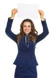 Mujer de negocios feliz que muestra la hoja del papel en blanco Fotografía de archivo libre de regalías