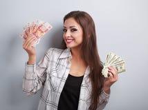 Mujer de negocios feliz que piensa esa moneda para elegir, dólares de o Fotografía de archivo libre de regalías