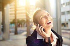 Mujer de negocios feliz que ríe en el teléfono móvil afuera Imagen de archivo