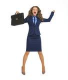 Mujer de negocios feliz que salta con la cartera foto de archivo
