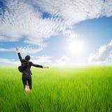 Mujer de negocios feliz que salta en campo verde   Foto de archivo libre de regalías