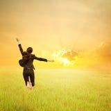 Mujer de negocios feliz que salta en campo y puesta del sol verdes del arroz Foto de archivo