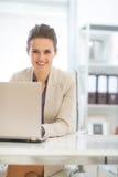 Mujer de negocios feliz que trabaja en el ordenador portátil en oficina Fotos de archivo