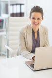 Mujer de negocios feliz que trabaja en el ordenador portátil en oficina Foto de archivo