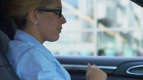 Mujer de negocios furiosa que jura en el teléfono móvil, teléfono que lanza fuera del automóvil metrajes