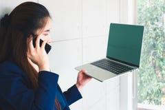 Mujer de negocios hermosa asiática que habla y que mira datos sobre el ordenador portátil fotografía de archivo libre de regalías