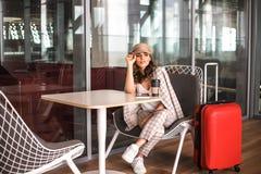 Mujer de negocios hermosa con la tableta que espera su vuelo en un aeropuerto fotografía de archivo