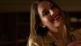 Mujer de negocios hermosa con los vidrios que sonríe y que liga encantador Fondo oscuro almacen de video