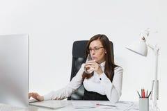 Mujer de negocios hermosa en el funcionamiento del traje y de vidrios en el ordenador con los documentos en oficina ligera fotos de archivo