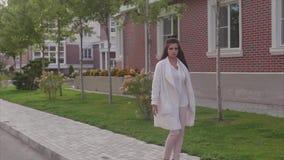 Mujer de negocios hermosa joven acertada que camina abajo de la calle almacen de metraje de vídeo