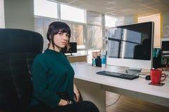 Mujer de negocios hermosa joven en una chaqueta oscura que se sienta en el lugar de trabajo cerca del ordenador en la silla de la Fotografía de archivo
