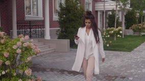 Mujer de negocios hermosa joven que camina abajo de la calle usando su smartphone almacen de metraje de vídeo