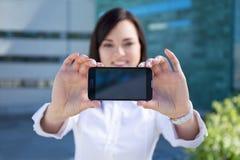 Mujer de negocios hermosa joven que muestra smartphone con el SCR en blanco Foto de archivo libre de regalías
