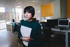 Mujer de negocios hermosa joven que presenta con los papeles en el fondo del espacio de oficina Secretaria con los documentos Imagenes de archivo