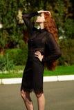 Mujer de negocios hermosa joven que se coloca al aire libre en traje negro Imagen de archivo