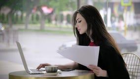 Mujer de negocios hermosa joven que se sienta en una tabla con los documentos en manos y los trabajos en el ordenador portátil en almacen de video