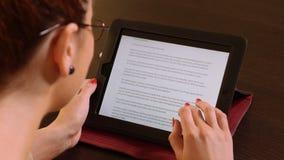 Mujer de negocios hermosa joven que se sienta en una tabla y que lee en la PC de la tableta metrajes