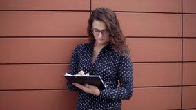 Mujer de negocios hermosa joven que trabaja con los documentos que colocan el edificio cercano del negocio almacen de video