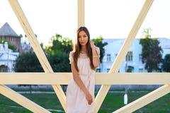 Mujer de negocios hermosa que presenta al aire libre en un día soleado brillante, vestido rosado, con el pelo moreno largo, en el imagenes de archivo