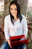 Mujer de negocios hermosa que se sienta con el ordenador portátil debajo de un árbol Fotografía de archivo libre de regalías
