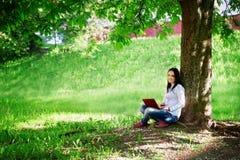 Mujer de negocios hermosa que se sienta con el ordenador portátil debajo de un árbol Imagen de archivo libre de regalías