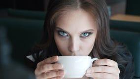 Mujer de negocios hermosa que se sienta en el café, café de consumición, mirando la cámara almacen de metraje de vídeo