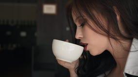 Mujer de negocios hermosa que se sienta en el café, café de consumición, mirando la cámara metrajes