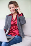 Mujer de negocios hermosa que sostiene el ordenador portátil que habla en el teléfono móvil imagen de archivo