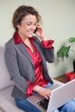 Mujer de negocios hermosa que sostiene el ordenador portátil que habla en el teléfono móvil fotos de archivo libres de regalías