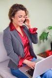 Mujer de negocios hermosa que sostiene el ordenador portátil que habla en el teléfono móvil imágenes de archivo libres de regalías