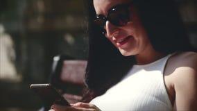 Mujer de negocios hermosa de un aspecto caucásico usando la tecnología elegante app del teléfono que se sienta en las calles de u almacen de metraje de vídeo