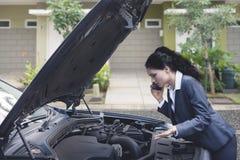 Mujer de negocios india trastornada que habla en el teléfono que pide una ayuda del mecánico fijar el coche analizado Fotografía de archivo libre de regalías