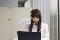 Mujer de negocios infeliz delante del ordenador portátil en oficina Imágenes de archivo libres de regalías