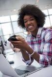 Mujer de negocios informal afroamericana que trabaja en la oficina Fotos de archivo libres de regalías