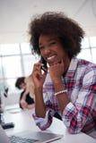 Mujer de negocios informal afroamericana que trabaja en la oficina Foto de archivo libre de regalías