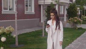 Mujer de negocios joven acertada que camina abajo de la calle usando su smartphone almacen de metraje de vídeo