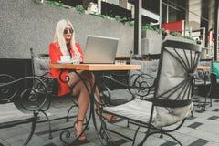 Mujer de negocios joven atractiva que trabaja en el ordenador portátil en café al aire libre fotografía de archivo libre de regalías