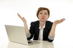 Mujer de negocios joven atractiva que trabaja en su ordenador subrayado, desesperado y abrumado imágenes de archivo libres de regalías