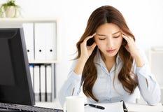 mujer de negocios joven cansada que trabaja en oficina imagenes de archivo