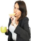 Mujer de negocios joven con café y tostada untada con mantequilla caliente Fotos de archivo