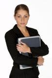 Mujer de negocios joven con la carpeta de los brazos alrededor de la computadora portátil Imagenes de archivo