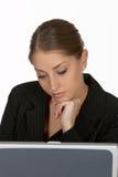 Mujer de negocios joven con la mano en la barbilla en la computadora portátil fotos de archivo libres de regalías