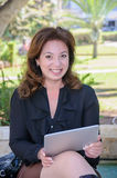 Mujer de negocios joven con la tableta en un banco de parque Foto de archivo