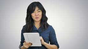 Mujer de negocios joven con la tableta que presenta el proyecto que mira la cámara en el fondo blanco almacen de metraje de vídeo