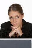 Mujer de negocios joven con las manos plegables en la computadora portátil Foto de archivo libre de regalías