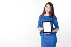 Mujer de negocios joven confiada que coloca y que sostiene la tableta digital de la pantalla en blanco para el presente algo en b Imagenes de archivo