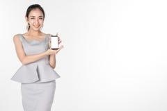 Mujer de negocios joven confiada que coloca y que sostiene la tableta digital de la pantalla en blanco para el presente algo en b Imagen de archivo